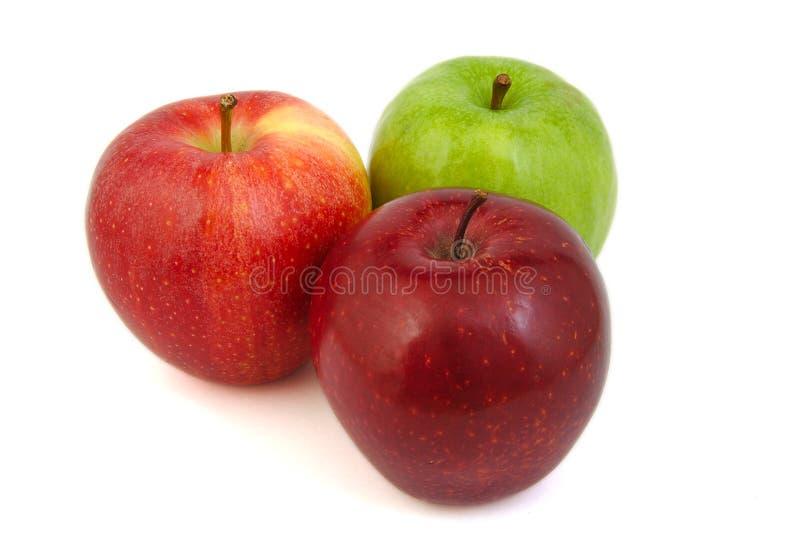Un insieme di tre rossi e delle mele verdi fotografia stock