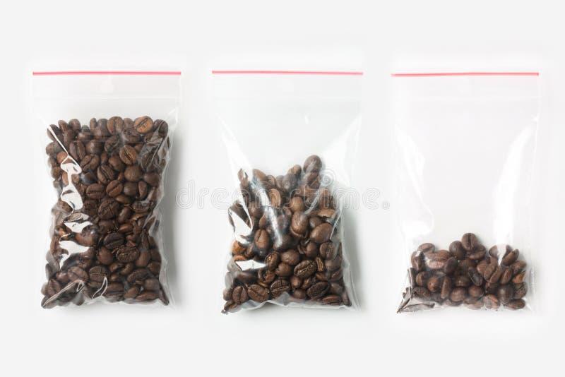 Un insieme di tre VUOTI, MEZZE E borse trasparenti di plastica PIENE della chiusura lampo con i chicchi di caffè isolati su bianc fotografie stock