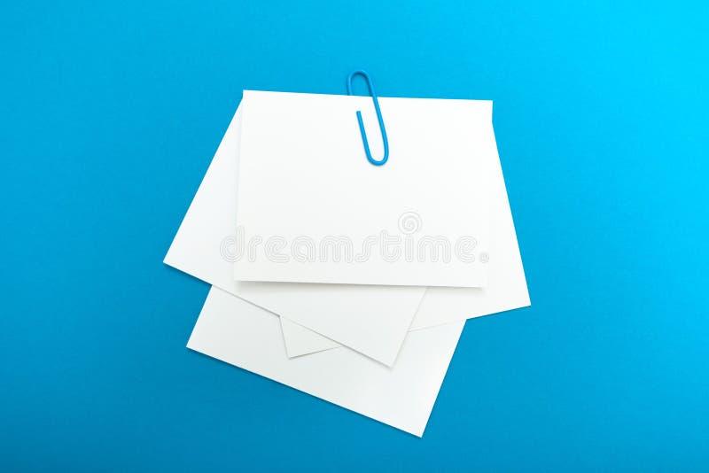 Un insieme di una nota di carta memorabile collegata da una graffetta su un fondo blu Una disposizione vuota immagine stock