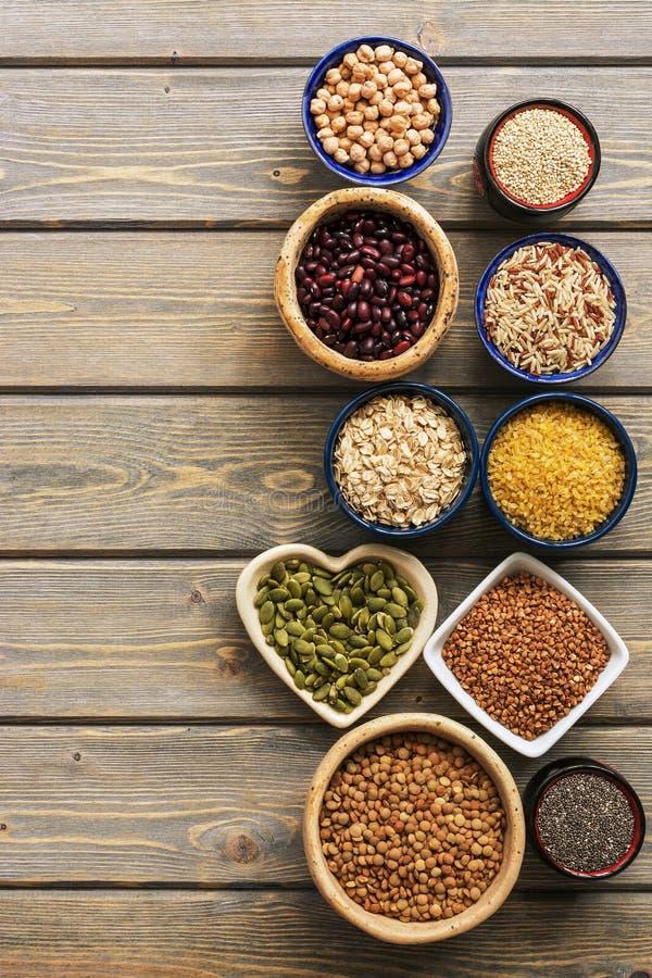 Un insieme di vari superfoods, interi grani, fagioli, semi, legumi in ciotole su una tavola di legno della plancia Vista superior immagine stock libera da diritti