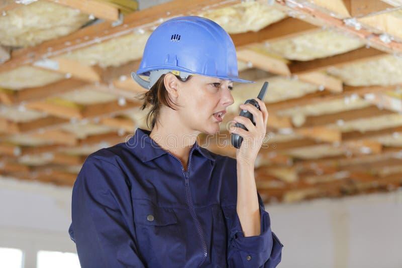 Un inspector en casco con walkie talkie en un almacén foto de archivo