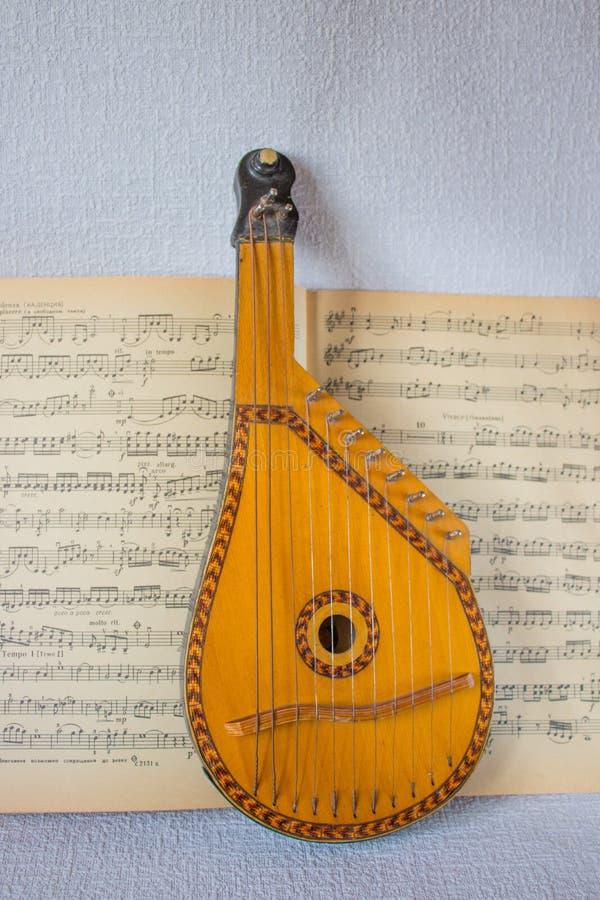 Un instrumento musical, un bandura, está situado en un libro de música abierto fotografía de archivo libre de regalías