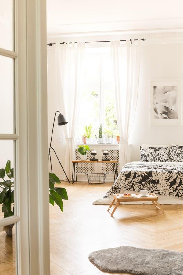 Un intérieur en bois de chambre à coucher de plancher avec un lit et un plateau de petit déjeuner Fenêtre avec les rideaux transp image stock