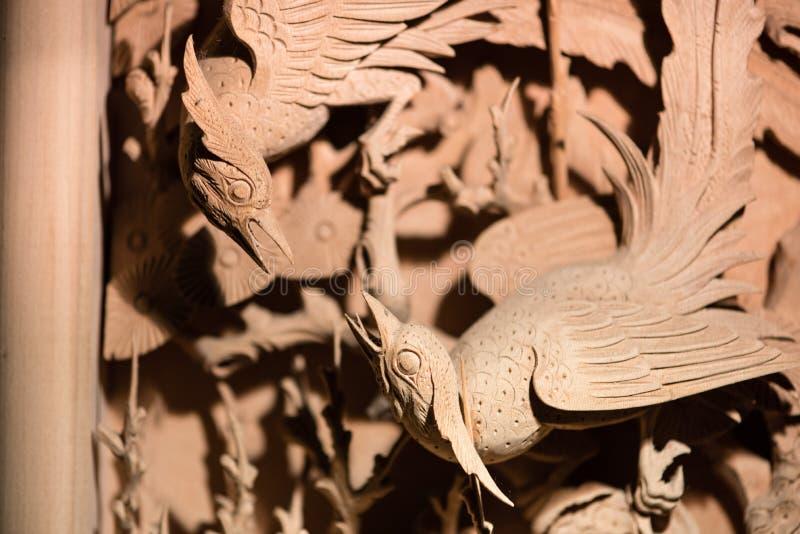 Un intaglio del legno del cinese tradizionale di un combattimento di due uccelli immagine stock libera da diritti