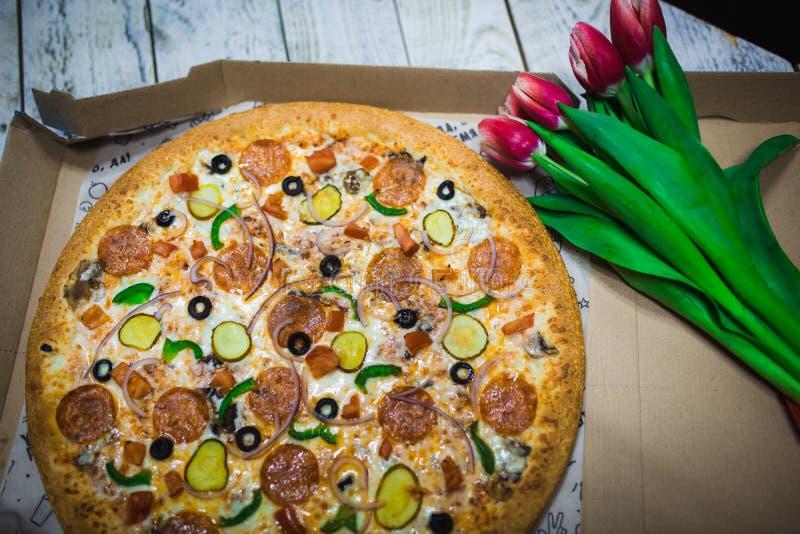 Un'intera pizza con le olive, pomodori, formaggio, cetrioli sulla tavola con i tulipani rossi fotografia stock libera da diritti