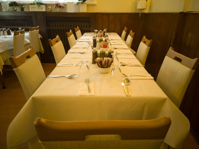 Un interior del restaurante con las tablas y las sillas viejas de lujo foto de archivo