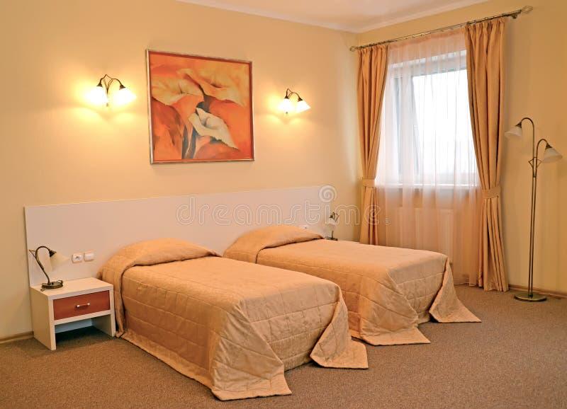 Un interno della camera da letto con due letti a colori i colori caldi fotografie stock libere da diritti