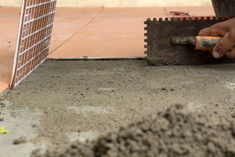 Un intonacatore sta piastrellando a casa, il rinnovamento adesivo della pavimentazione in piastrelle a immagine stock
