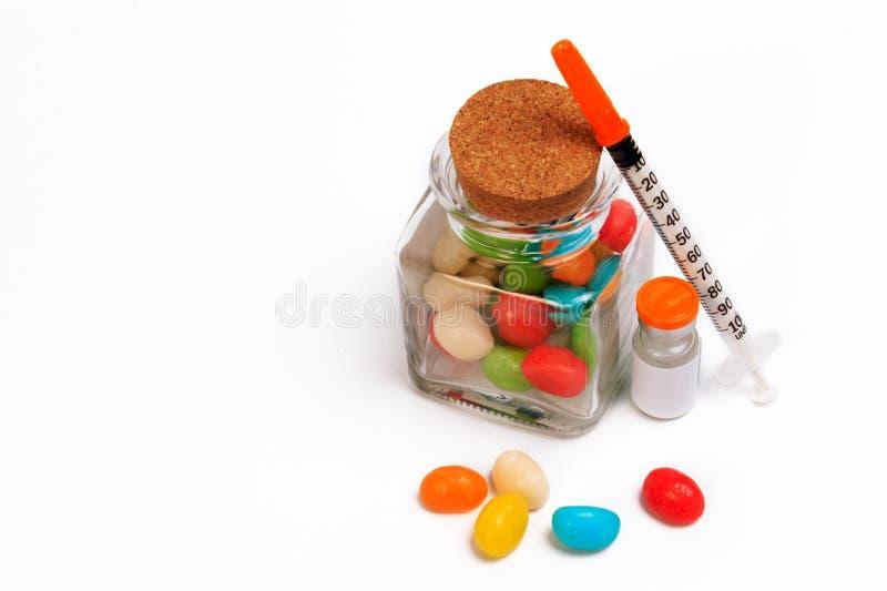 Un isolato della bottiglia della caramella e della siringa su fondo bianco immagini stock libere da diritti