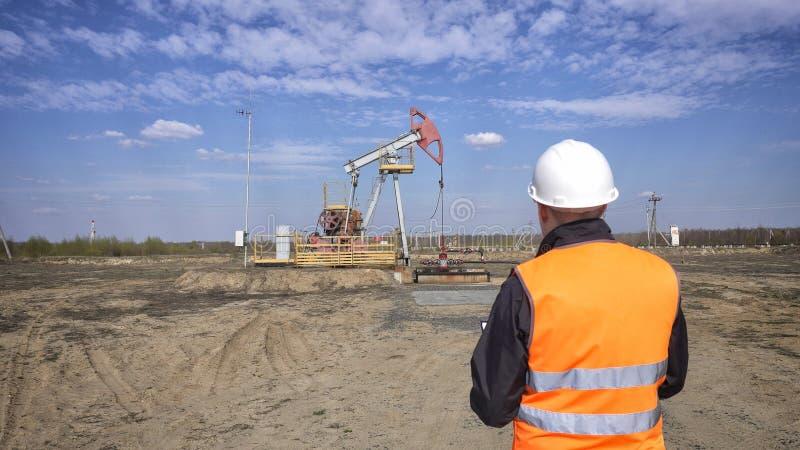 Un ispettore-operatore maschio in una maglia del segnale ed in un casco bianco registra le letture circa il petrolio, il gas ed i immagine stock