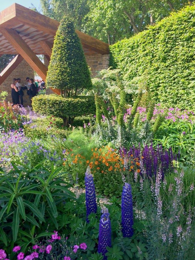 Un jardín brillante con las flores y los árboles foto de archivo libre de regalías