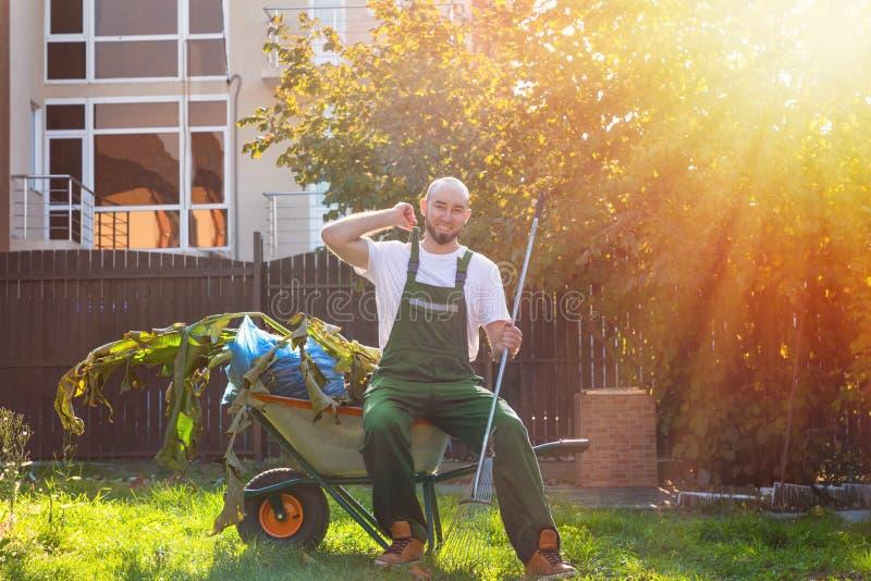 Un jardinier dans sourires uniformes verts, se reposant sur un chariot avec des feuilles Le soleil brille brillamment image libre de droits
