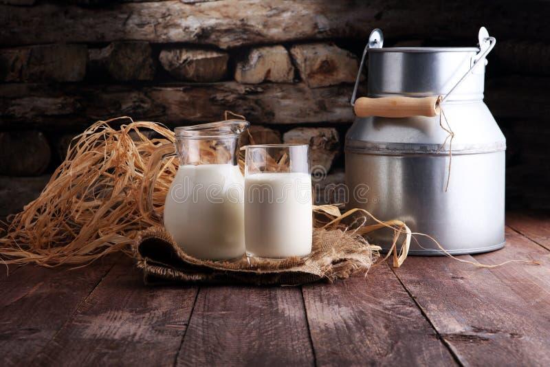 Un jarro de leche y de vidrio de leche en una tabla de madera fotos de archivo