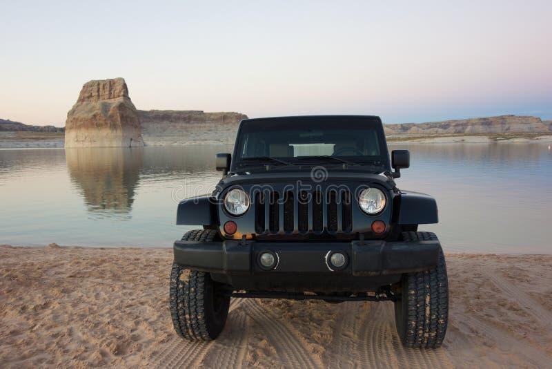 Un jeep parqueó en las orillas del lago powell fotos de archivo