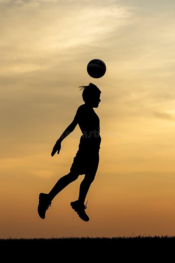 Un jefe del balón de fútbol en la puesta del sol imagen de archivo libre de regalías