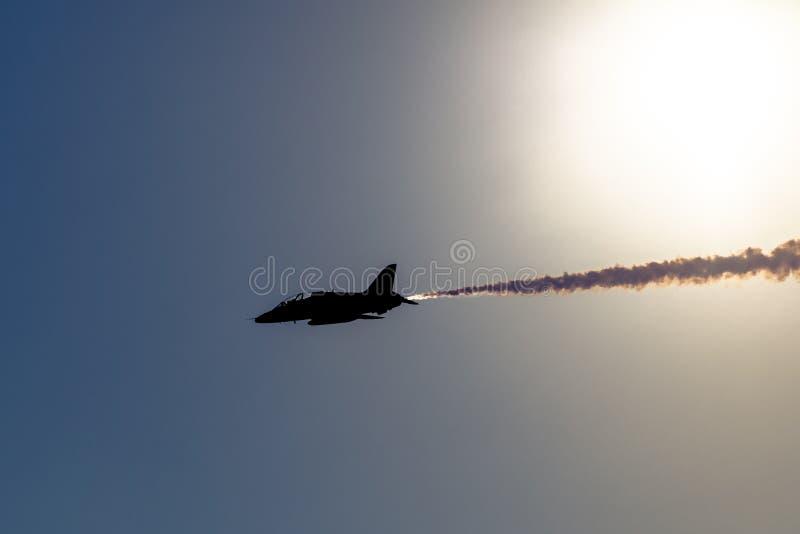 Un jet rápido aeroacrobacia con humo encendido se siluetea contra el sol fotografía de archivo