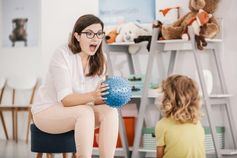 Un jeu sensoriel avec une boule bleue a joué par un enfant professionnel t photo libre de droits