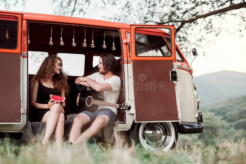 Un jeune ajouter à la guitare dehors sur une promenade en voiture par la campagne, parlant photo stock