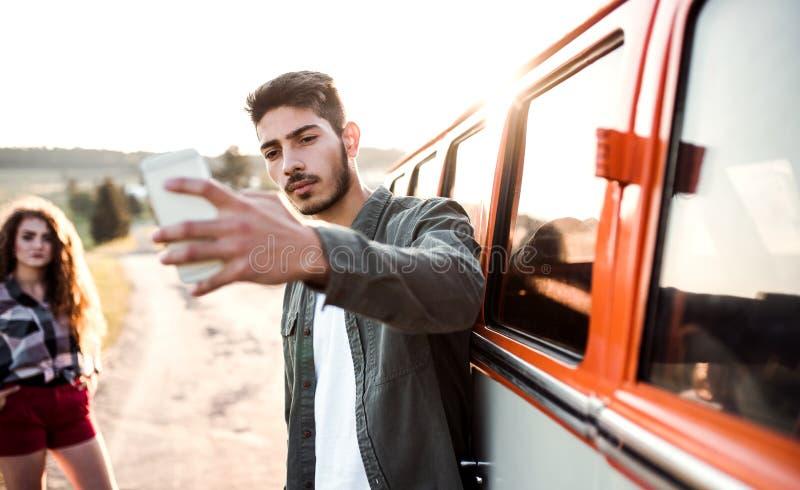 Un jeune ajouter au smartphone en une voiture sur une promenade en voiture par la campagne, prenant le selfie image stock