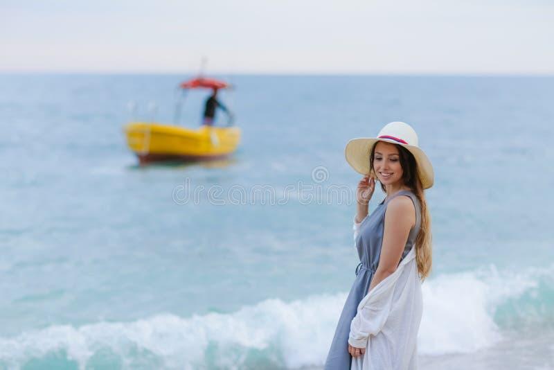 Un jeune amour de couples se reposant sur l'image courante de sourire de plage photographie stock