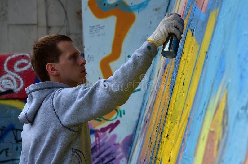 Un jeune artiste roux de graffiti peint un nouveau graffiti sur le mur photos stock