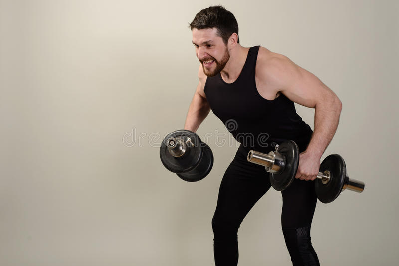 Un jeune athlète exécute un exercice avec des haltères sur le développement des muscles des épaules photo stock