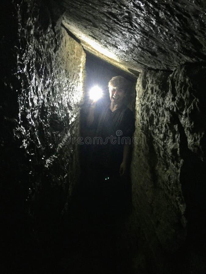 Un jeune aventurier explorant les cavernes le long de la traînée de lac berg photos libres de droits