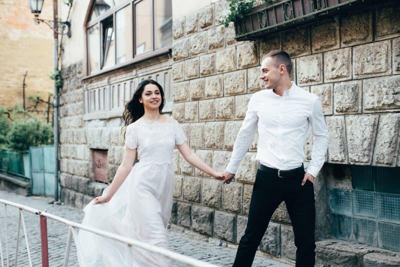 Un jeune, bienveillant couple marche par les rues de la ville image libre de droits