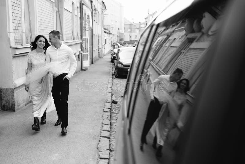 Un jeune, bienveillant couple marche par les rues de la ville photographie stock libre de droits