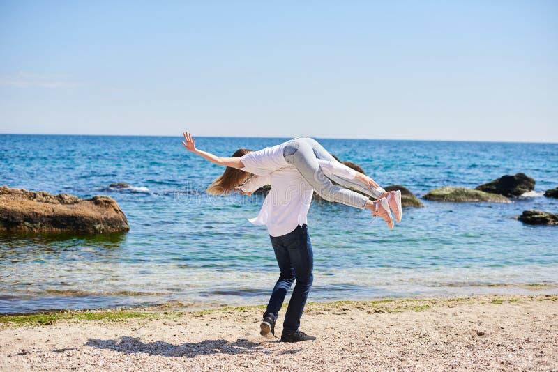 Un jeune couple affectueux ?treignant et embrassant sur la plage dans le jour ensoleill? Deux amants, homme et femme pr?s de l'ea photographie stock