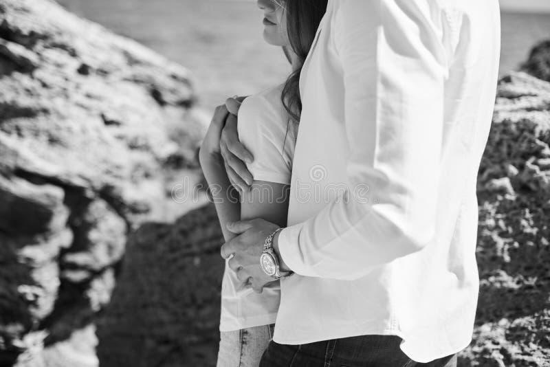 Un jeune couple affectueux ?treignant et embrassant sur la plage dans le jour ensoleill? Deux amants, homme et femme pr?s de l'ea images stock