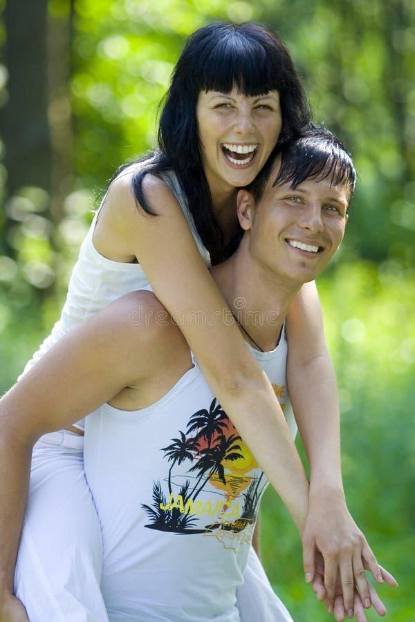 Un jeune couple ayant l'amusement dans le stationnement photo stock