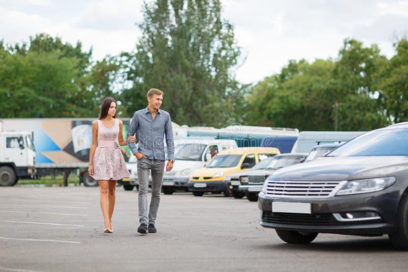 Un jeune couple choisit leur première voiture Les amants marchent autour de la caravane et regardent des voitures Q photographie stock libre de droits