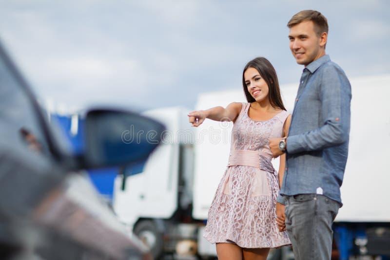 Un jeune couple choisit leur première voiture Les amants marchent autour de la caravane et regardent des voitures Q photos libres de droits