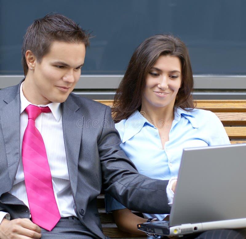 Un jeune couple d'affaires fonctionne à l'extérieur photographie stock