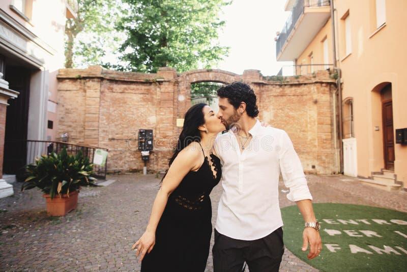 Un jeune couple d'amour appréciant une promenade dans la cour de la vieille ville Sur le fond, murs de briques rouges images stock