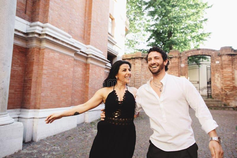 Un jeune couple d'amour appréciant une promenade dans la cour de la vieille ville Sur le fond, murs de briques rouges photos libres de droits