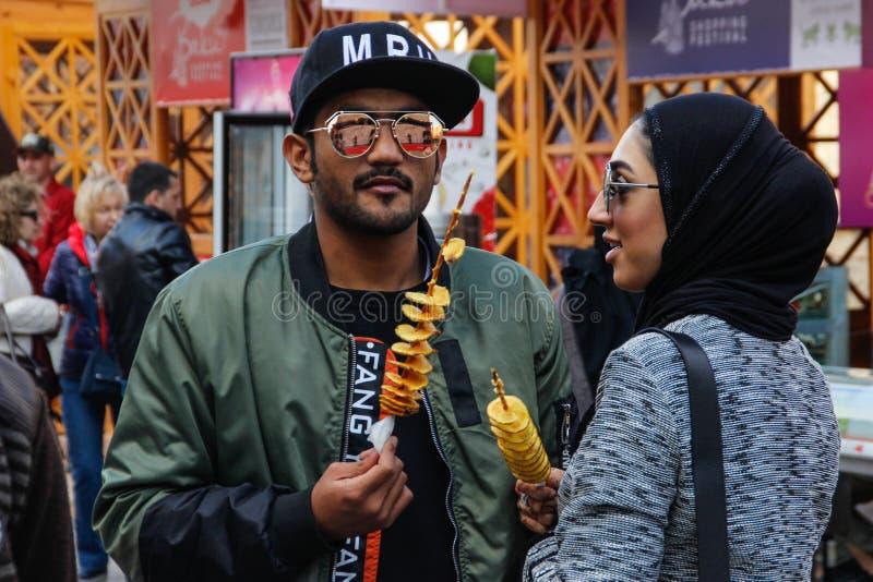 Un jeune couple d'Arezbijian dans le hijab et verres mangeant des pommes chips sur un bâton Nourriture de rue de l'Azerbaïdjan photos libres de droits