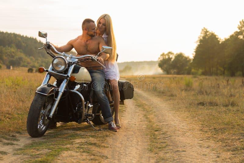 Un jeune couple dans l'amour sur une moto dans le domaine image stock