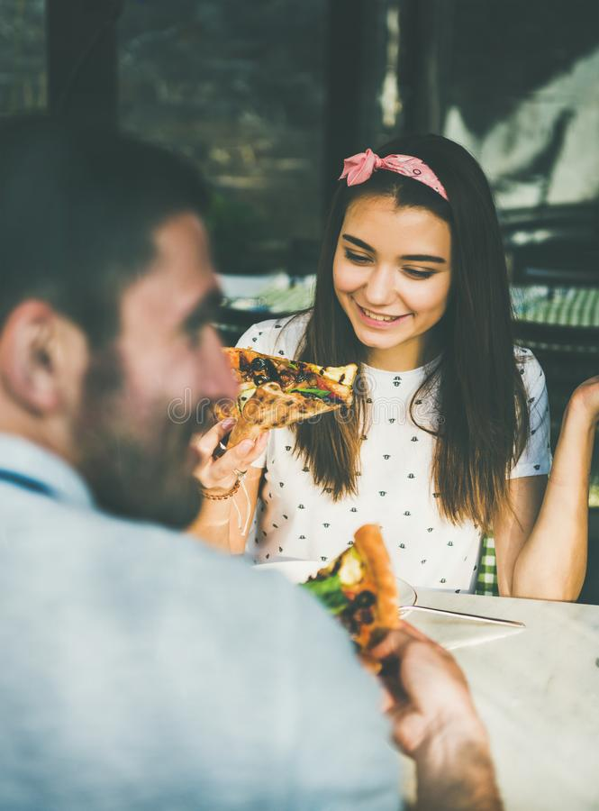Un jeune couple de caucasiens heureux qui mange de la pizza au café photos stock