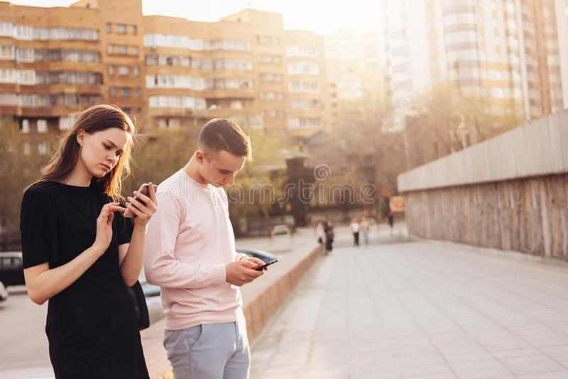 Un jeune couple des amis, adolescents, étudiants à l'aide des téléphones portables à la rue de ville image stock