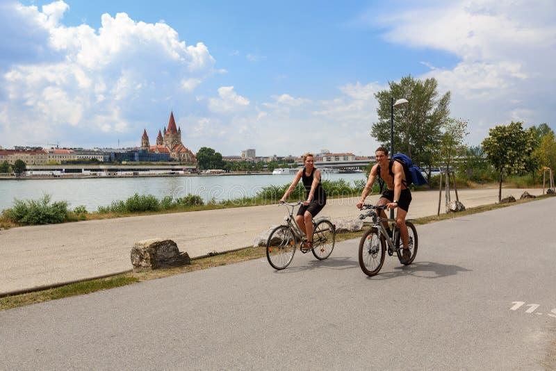 Un jeune couple des bicyclettes d'équitation sur l'île de Danube Vienne, Autriche photographie stock libre de droits