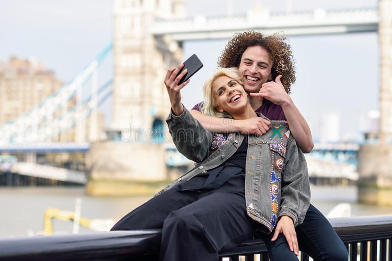Un jeune couple en selfie photographie au Tower Bridge image libre de droits