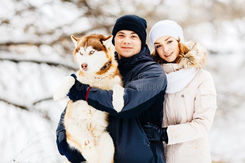 Un jeune couple marchant dans la forêt avec le chien de traîneau rouge de chien toned photo stock