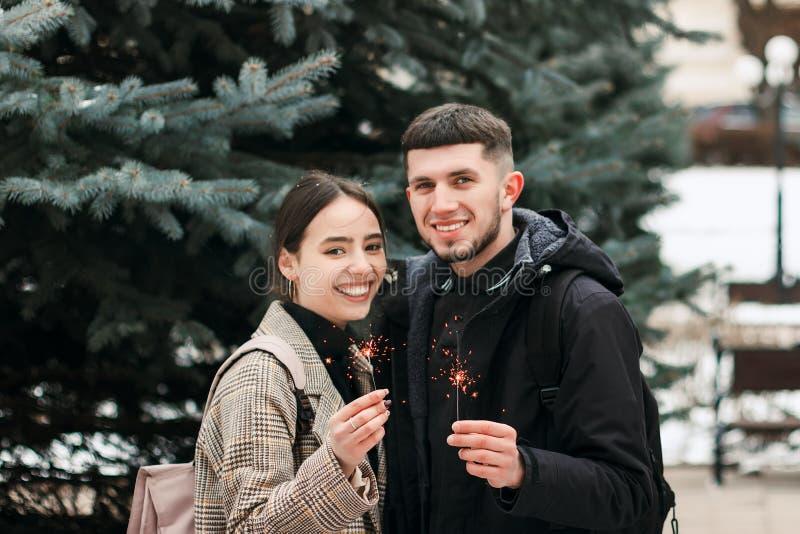 Un jeune couple riant avec des lumières de Bengale dans les mains photos stock