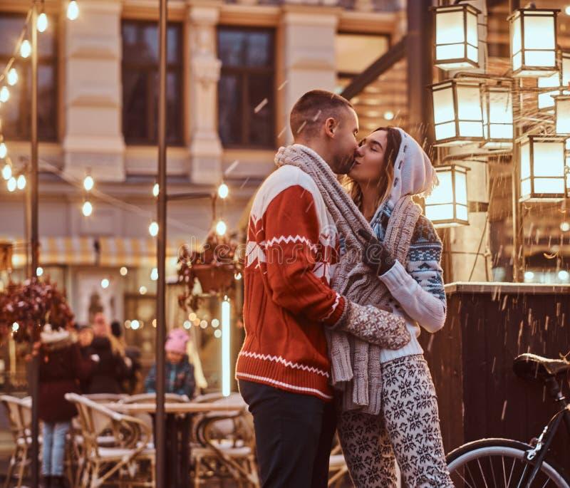 Un jeune couple romantique portant les vêtements chauds tenant des mains et embrassant la position dehors la nuit, appréciant la  images stock