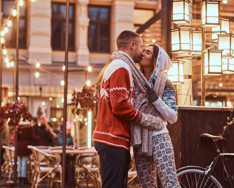 Un jeune couple romantique portant les vêtements chauds tenant des mains et embrassant la position dehors la nuit, appréciant la  photos stock