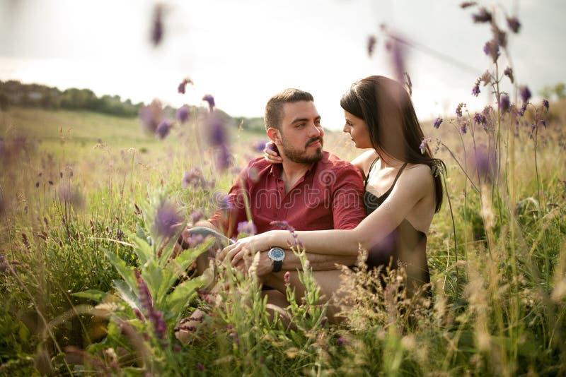 Un jeune couple se repose dans un pré photo stock
