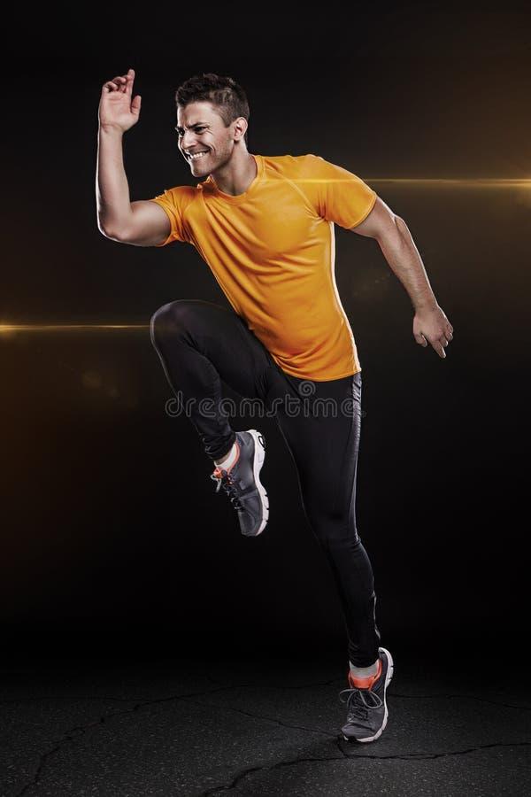 Un jeune coureur de sprinter d'homme caucasien fonctionnant dans le St de silhouette photo stock