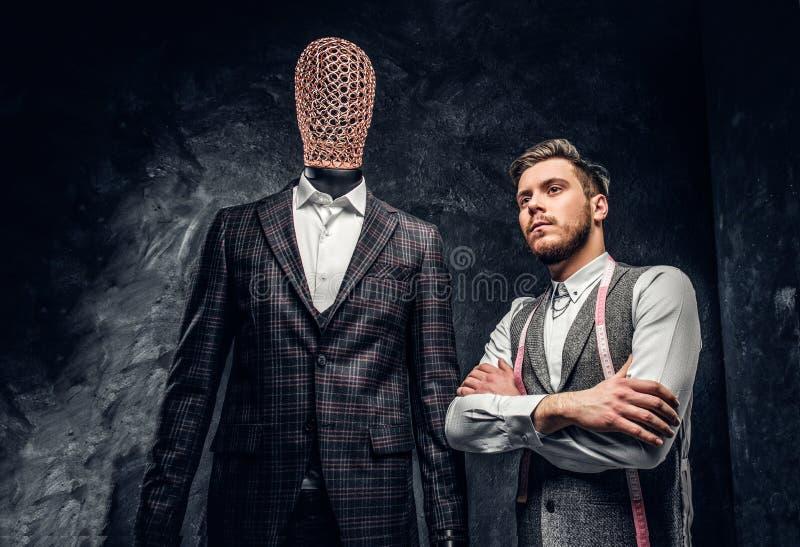 Un jeune couturier sûr posant à côté d'un mannequin dans le costume des hommes faits sur commande exclusifs dans un tailleur fonc photos stock
